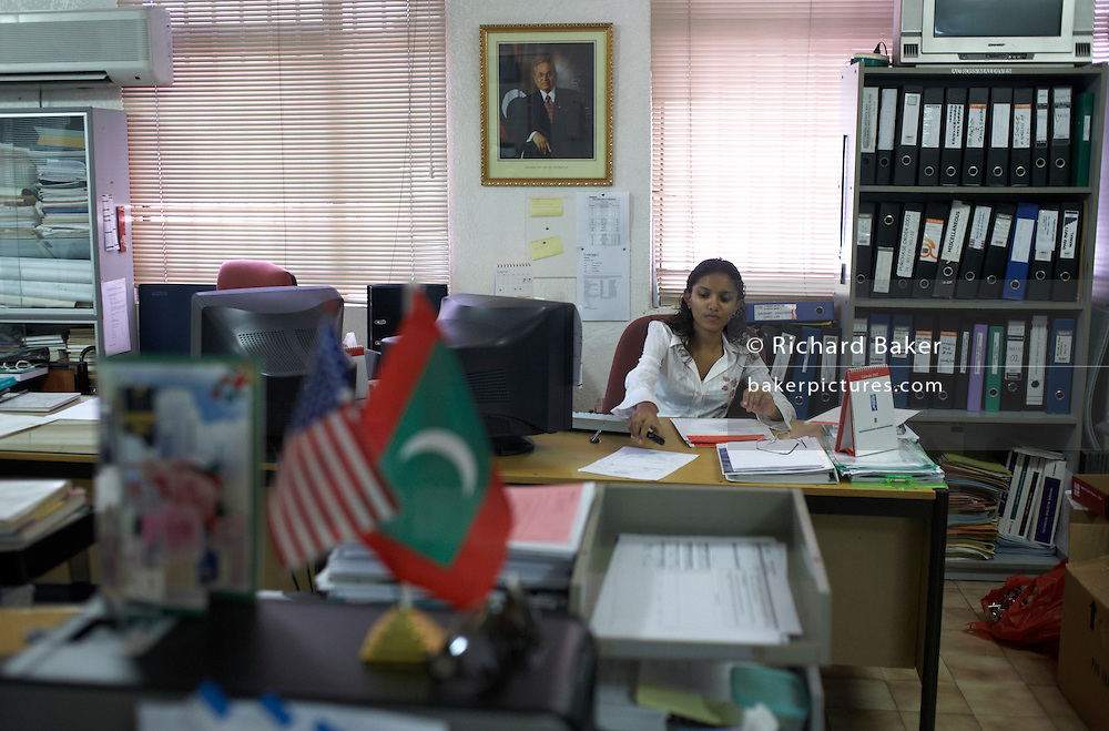 Female employee of Cyprea Marine Foods works beneath portrait of Maldives president Gayoom in capital Male.