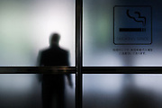 A smoker in a smoking area of a building in Roppongi, Tokyo, Japan Thursday June 27th 2013