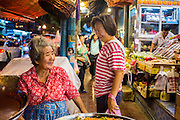 18 SEPTEMBER 2013 - BANGKOK, THAILAND:  A woman talks to a pastry vendor in the Chinatown section of Bangkok. Thailand in general, and Bangkok in particular, has a vibrant tradition of street food and eating on the run. In recent years, Bangkok's street food has become something of an international landmark and is being written about in glossy travel magazines and in the pages of the New York Times.     PHOTO BY JACK KURTZ