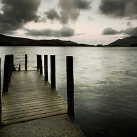 A small wooden jetty looking out over a lake with stormy clouds over a dark headland
