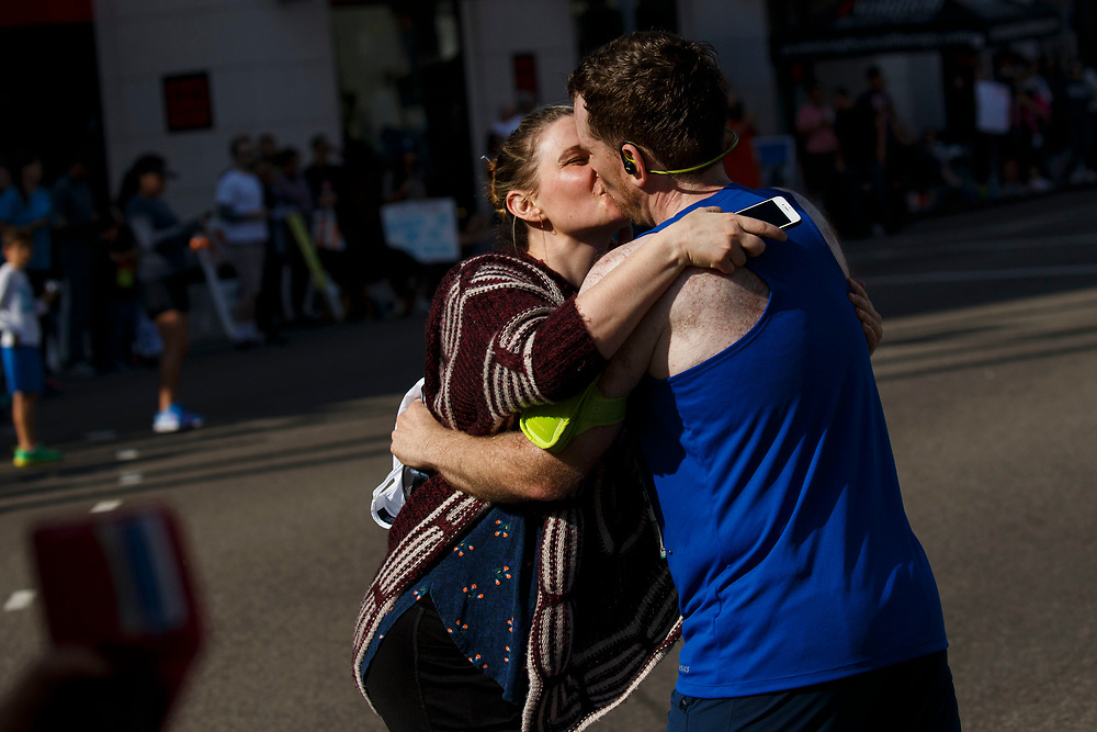 "Runner Aaron Eaton, right, kisses his girlfriend Marissa Tait as she cheers him on at Rodeo Drive after mile marker 17 during the 32nd annual Los Angeles Marathon on Sunday morning, March 19, 2017 in Beverly Hills, Calif.  The 26.2-mile ""Stadium to the Sea"" route begins at Dodger Stadium and ends at Ocean and California avenues in Santa Monica. © 2017 Patrick T. Fallon"