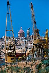MALTA VALETTA JUL00 - Two cranes of the Maltese dry docks frame the view on one of Malta's many churches.....jre/Photo by Jiri Rezac....© Jiri Rezac 2000....Tel:   +44 (0) 7050 110 417..Email: info@jirirezac.com..Web:   www.jirirezac.com