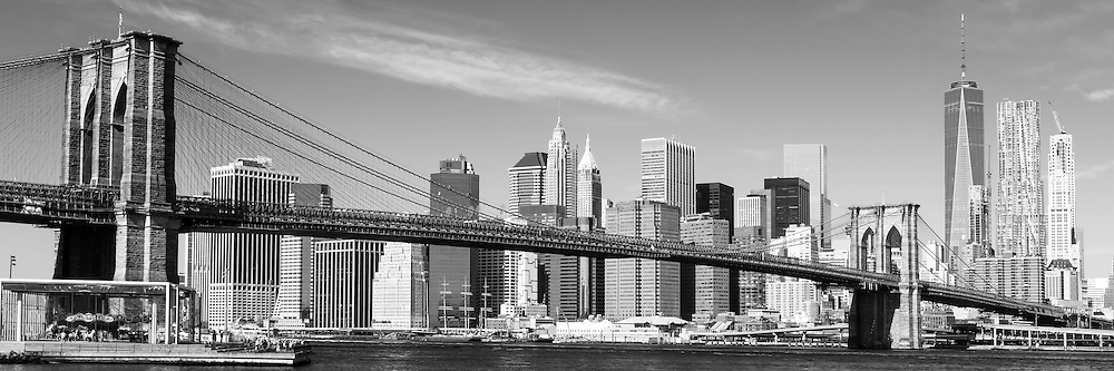 The New York City skyline rises behind the Brooklyn Bridge and a warm Fall morning.