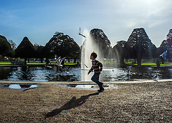 © Licensed to London News Pictures. 31/10/2014. Hampton, UK. A young boy chases birds as he runs past a fountain. People enjoy the warm weather at Hampton Court Palace today 31st October 2014. forecasters are predicting It could be the warmest halloween on record. Photo credit : Stephen Simpson/LNP