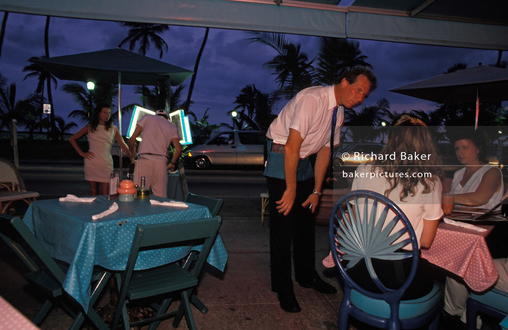 As a couple inspect the menu on the sidewalk, a waiter attends to customers at an outdoor restaurant and bar on Ocean Drive,  on 15th May 1996, in Miami Beach, Florida, USA