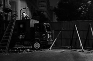 In a street accessing Tahrir Square, a wrecked police truck is now a part of the barricade closing that street.<br /> A pro democracy protester is on the watch for roaming groups of Mubarak supporters. 05 February 2011.