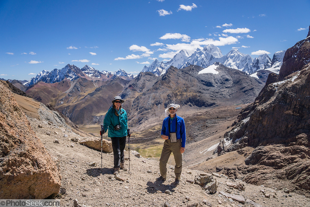 "Trekkers reach Punta Cuyoc (16,200 feet or 4950 m pass), beneath Nevados Puscanturpa. Day 5 of 9 days trekking around the Cordillera Huayhuash in the Andes Mountains, Peru, South America. The most prominent snowy peak is Siula Grande (20,814 ft or 6344 m), which was the subject of the gripping 2003 British docudrama ""Touching the Void."" In 1985, climbers Joe Simpson and Simon Yates scaled the treacherous West Face of Siula Grande, but after Joe broke his leg, their descent became one of the most amazing survival stories in mountaineering history. The 2003 movie is based upon Joe Simpson's harrowing book, ""Touching the Void: The True Story of One Man's Miraculous Survival."" For licensing options, please inquire."
