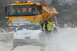 © Licensed to London News Pictures. 2/03/2018. Brynmawr, Blaenau Gwent,, South Wales, UK. Men from a gritting truck help a stranded motorist who has got stuck near the Heads of Valley road near Brynmawr. People battlle against the blizzard, snowdrifts and horrendous weather conditions as Storm Emma continues without mercy at Brynmawr in South Wales (the highest town in Wales.)  Photo credit: Graham M. Lawrence/LNP