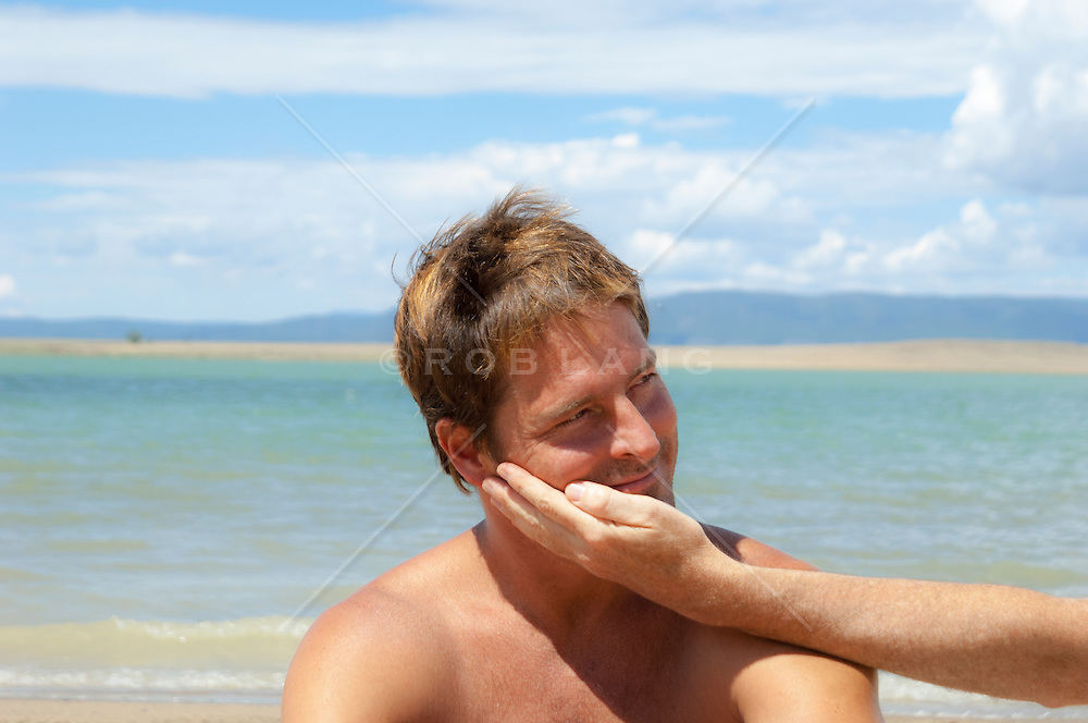 man touching another man's face outdoors at a lake in New Mexico
