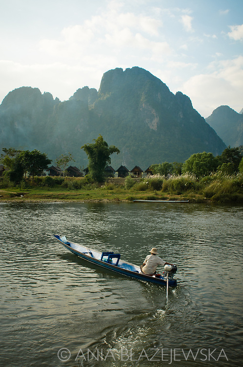 Laos, Vang Vieng. A fisherman coming back home and the beautiful scenery full of outstanding limestones in the background.