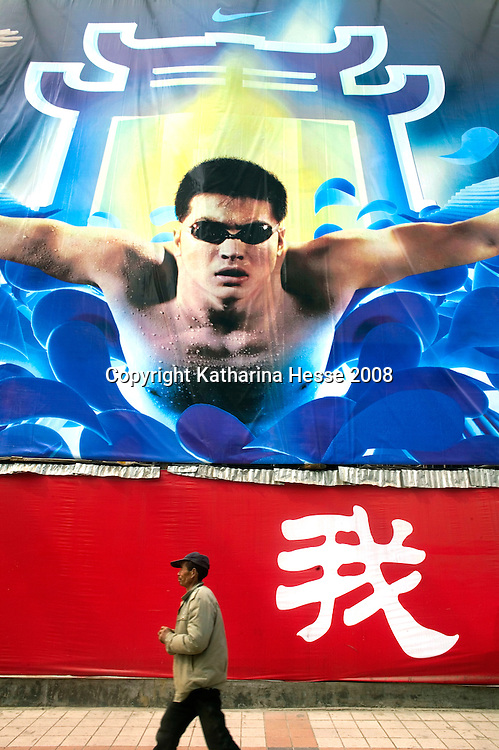 BEIJING, MARCH 21, 2008 :  a man walks past a billboard outside the Oriental Plaza shopping mall.