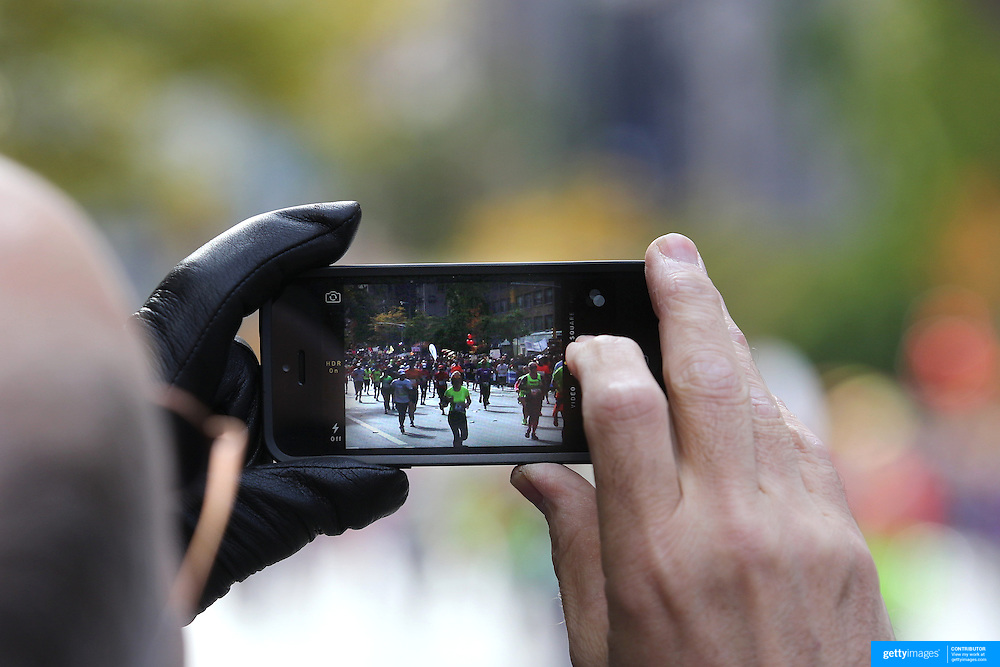 A man photographs runners with an iPhone as they make their way along First Avenue in Manhattan, New York, during the ING New York Marathon. New York, USA. 3rd November 2013. Photo Tim Clayton