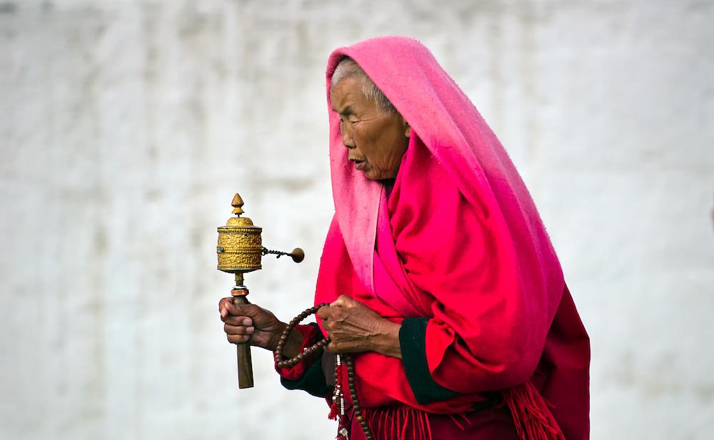 A woman spinsher prayer wheel whilst walking around the temple in Thimphu, Bhutan.