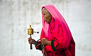 A woman spinsher prayer wheel whilst walking around the temple in Thimphu, Bhutan.