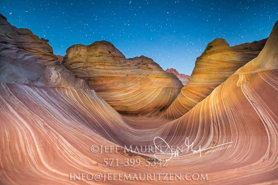 A shooting star passes over the Wave sandstone rock formation, located in Coyote Buttes North, Paria Canyon, Vermillion Cliffs Wilderness.