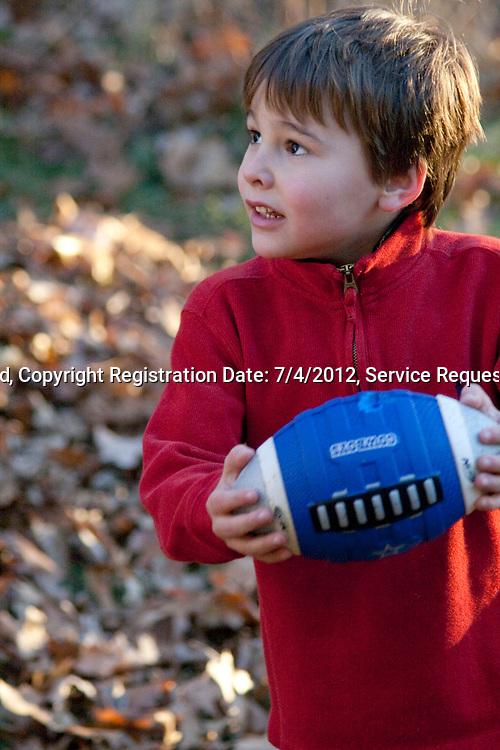 Boy age 5 playing touch football in backyard. Champlin Minnesota MN USA