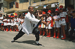 Experts demonstrating t'ai chi Ch'uan on the streets of Havana; Cuba; being watched by school children,