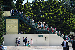 © Licensed to London News Pictures. 21/06/2018. London, UK. Racegoers cross a bridge as they arrive for Ladies Day at Royal Ascot at Ascot racecourse in Berkshire, on June 21, 2018. The 5 day showcase event, which is one of the highlights of the racing calendar, has been held at the famous Berkshire course since 1711 and tradition is a hallmark of the meeting. Top hats and tails remain compulsory in parts of the course. Photo credit: Ben Cawthra/LNP