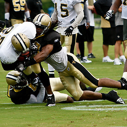 August 3, 2010; Metairie, LA, USA; New Orleans Saints safety Usama Young (28) hits running back Reggie Bush (25) on a run during a training camp practice at the New Orleans Saints practice facility. Mandatory Credit: Derick E. Hingle-US PRESSWIRE