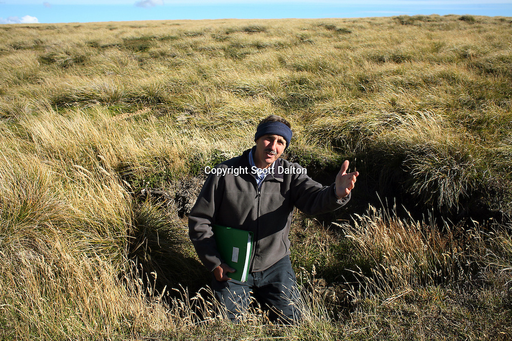 Patrick Watts, who ran the radio station during the war, now gives tours of the battlefields, like this one just outside of Goose Green on Monday, March 19, 2007. Watts is showing a foxhole that was used in a battle between the British and Argentina forces. (Photo/Scott Dalton)