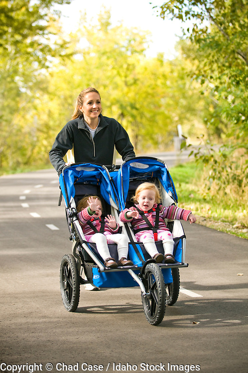 Idaho, Boise Greenbelt that runs along the Boise River. Mother with twin girls in stroller running. MR