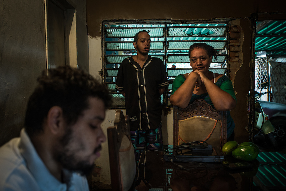 """MARACAY, VENEZUELA - JULY 16, 2016: Evelin RodrÍguez (right) hangs out at home with her two schizophrenic sons, Gerardo (center) and Accel (left). Evelin is a lawyer, but has quit all of her work since Accel attempted to cut off his arm after three weeks without his medicine. Too afraid to leave her adult sons alone, Evelin now spends her days looking after Accel and Gerardo while her husband works, or searching pharmacies for hours  for the psychiatric drugs that her sons need, which are very difficult to find, because of nationwide shortages.  """"I am tired,"""" she said. """"This is too much sometimes, and I admit it, I haven't been looking as much as I needed to,"""" she said. PHOTO: Meridith Kohut for The New York Times"""