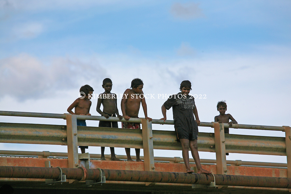 Local kids line up to jump off the bridge at Fitzroy Crossing as the river rises in the Kimberley wet season.