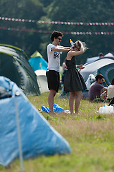 © Licensed to London News Pictures. 18/07/2014. Southwold, UK.   Festival goers apply sunscreen on a hot sunny morning next to their tents at Latitude Festival 2014 Day 1. Today is expected to be the hottest day of the year with temperatures forecast to reach 32 degrees centigrade.   Latitude is an British annual music festival.  Photo credit : Richard Isaac/LNP