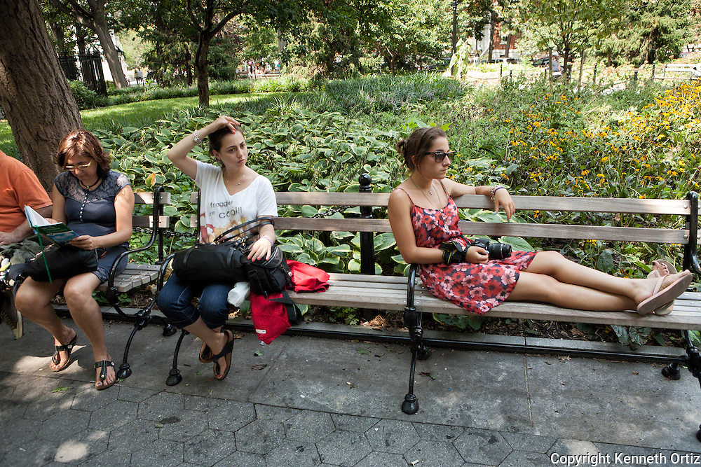 A group of people resting on park benches on a hot summer day in down town Manhattan in Washington Square Park.