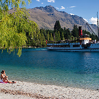 "Wakatipu beach and the TSS Earnslaw with the Remarkables mountain range in the background. According to ""Wikipedia"" - The TSS Earnslaw is a 1912 Edwardian vintage twin screw steamer plying the waters of Lake Wakatipu in New Zealand. It is one of the oldest tourist attractions in Central Otago, and the only remaining commercial passenger-carrying coal-fired steamship in the southern hemisphere."