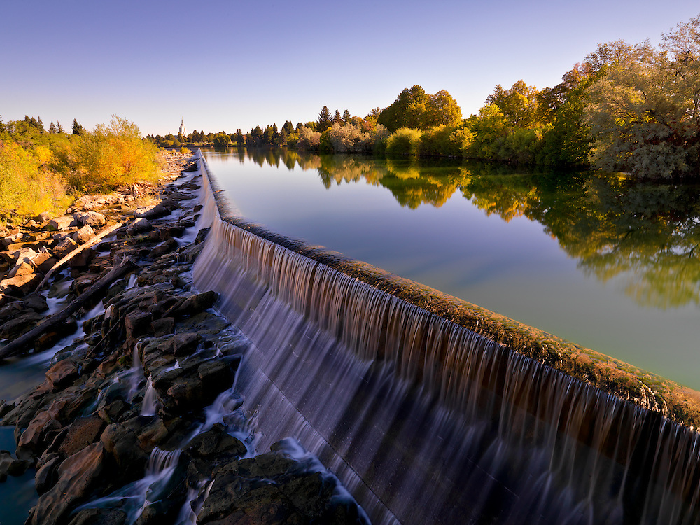 Manmade dam on the Snake River in downtown Idaho Falls in Eastern Idaho creates a center piece park area and Mormon Temple in background