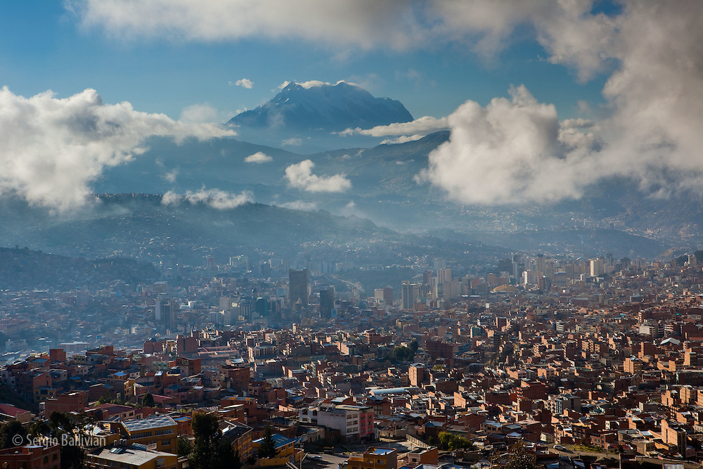 The sky-high capital city of La Paz, Bolivia  lies in a deep canyon below the Andes Mountains.  As the clouds lift after a rainstorm the peaks of the Cordillera Real reveal themselves, many reach heights of over 21,000 ft above sea level.
