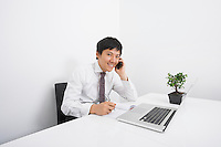 Portrait of happy businessman using cell phone while working at office desk