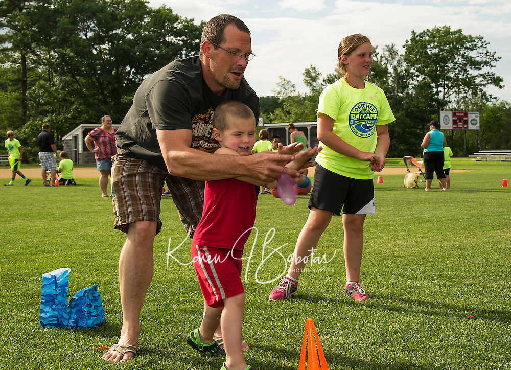 Jonathan McNeil and father Chris McNeil team up for the Balloon Toss game at the Opechee Peanut Carnival on Thursday evening.  (Karen Bobotas/for the Laconia Daily Sun)