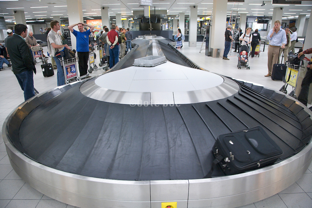 passengers waiting for there luggage at an airport