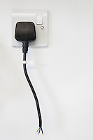 Frayed electrical cord with outlet attached on white wall