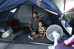 October 5, 2016 - Athens, Greece - An Afghan  with his son at their tent in a sports facility in the olympic complex at the former Athens airport of Athens, Greece on October 5, 2016.Almost 2,500 migrants and refugees, mainly Afghani, are housed at the former Athens airport site, and to an olympic complex used in the 2004 Olympics. In total 60.736 refugees and other migrants are stranded in Greece. (Credit Image: © Panayiotis Tzamaros/NurPhoto via ZUMA Press)