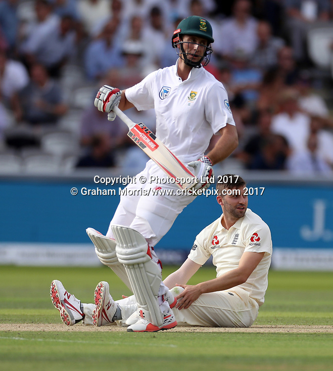 Bowler Mark Wood falls over as he appeals (in vain) for the lbw of Theunis de Bruyn (left) during the 1st Investec Test Match between England and South Africa at Lord's Cricket Ground. Photo: Graham Morris / www.cricketpix.com / www.photosport.nz