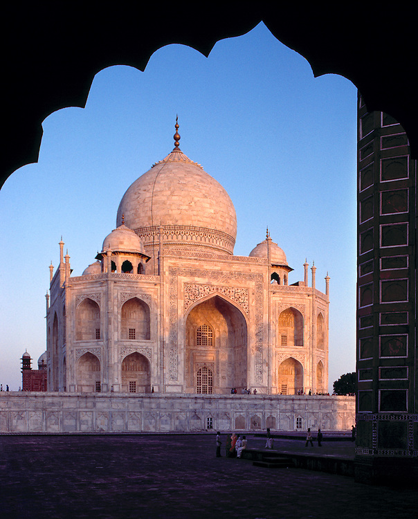 Viewed through a scalloped window, the first light of the sun reddens the Taj Mahal, in Agra, India.