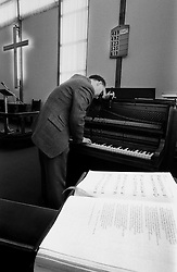 Partially sighted Paul Chrimes from Wolverhampton who is a member of the Association of Blind Piano Tuners. Pictured tuning an instrument at Roseville Methodist Church, Coseley, Bilston, West Midlands, England, UK.