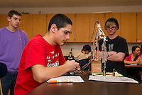 """Devon Loving and Michael Tierney look on as Justin Padua works Tierney's robotic arm to """"Find the Mass"""" during JoAnne Gilbert's Applied Physics class at LHS Monday afternoon.  (Karen Bobotas/for the Laconia Daily Sun)"""