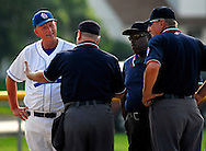 25 MAY 2010 -- FLORISSANT, Mo. -- St. Lois University High School baseball coach Steven Nicollerat (14) talks with the officials before they called Alex Geodeker for interference, ending the inning in the Junior BIllikens game against Hazelwood Central High School at Hazelwood Central Tuesday, May 25, 2010. SLUH won, 12-0. Photo © copyright 2010 by Sid Hastings.