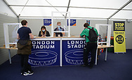 Staff are protected by screens in the accreditation centre during the Premier League match at the London Stadium, London. Picture date: 20th June 2020. Picture credit should read: David Klein/Sportimage