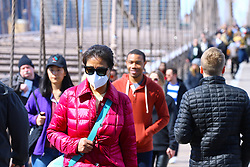 Tourists with face mask walk the Brooklyn Bridge on saturday afternoon in New York, NY on March 14, 2020. As of Saturday morning, New York State had 524 confirmed coronavirus cases.<br /> Photo by Dylan Travis/ABACAPRESS.COM