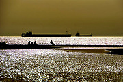 Silhouette of fishermen fishing on the Ashdod shore of the Mediterranean Sea, Israel. Ships waiting to enter the port of Ashdod in the background