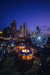 Downtown Aquarium with lit ferris wheel and Houston, Texas skyline at night.