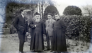 two young adult men posing with two priests 1920s