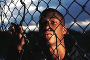 "Toy ""Troy"" Trice (15 years old) was hit by lightning during high school football practice in September of 1991. The strike tore a hole in his helmet, burned his jersey and blew his shoes off. He recovered from a two-day coma with burns and memory loss. Trice was photographed by the schoolyard fence near where he was struck by lightning. MODEL RELEASED (1993)"