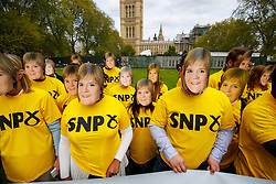 © Licensed to London News Pictures. 01/05/2015. LONDON, UK. Conservative supporters dressed in SNP shirts and wearing Nicola Sturgeon masks posing to highlight the possibility of the SNP propping up Labour leader Ed Miliband as Prime Minister at Victoria Tower Gardens, London on Friday, 1 May 2015. Photo credit : Tolga Akmen/LNP