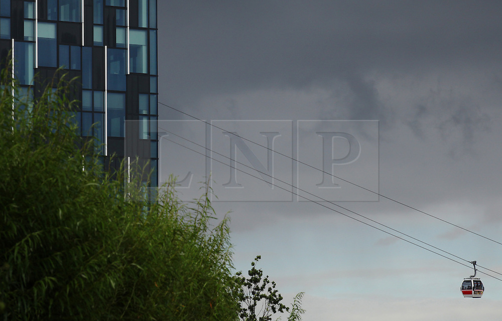 © Licensed to London News Pictures . 15/08/2013 . London, UK. Overcast sky with London's cable car in the background as the city expects heavy rains for tomorrow. Photo credit : /LNP